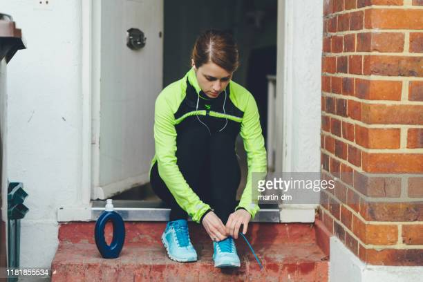 woman lacing running shoes before jogging - women trying on shoes stock pictures, royalty-free photos & images