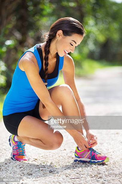 Woman lacing up her running shoes