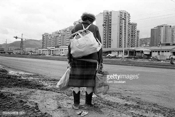 Woman laden with firewood makes her way home across the road known as Sniper Alley. During the 47 months between the spring of 1992 and February...