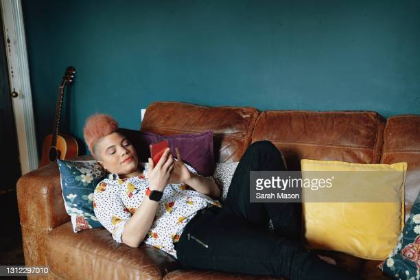 woman laid back on sofa texting - one mid adult woman only stock pictures, royalty-free photos & images