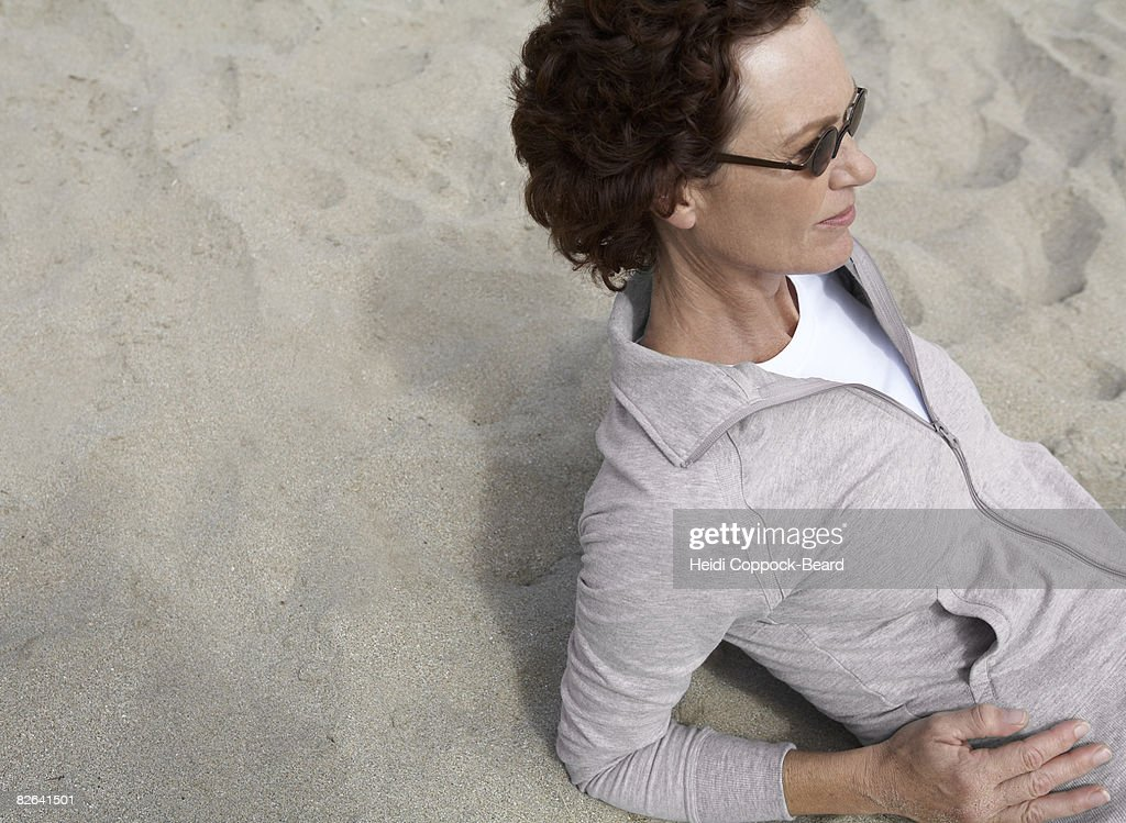 Woman laid on sand  : Stock Photo