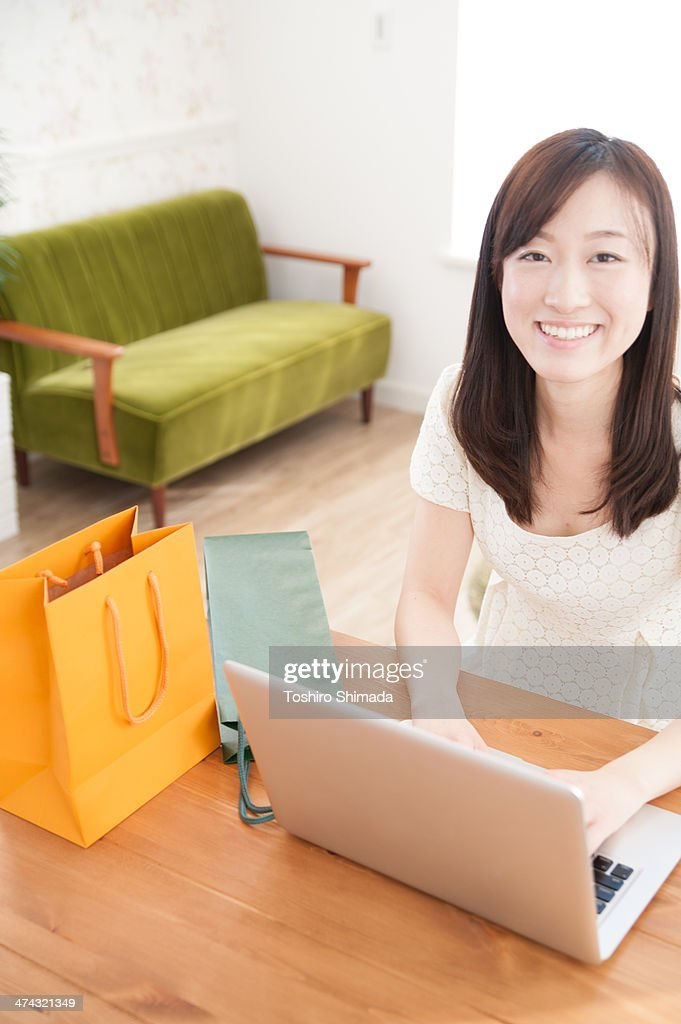 A woman laptoping on the table with shopping bags : Stock Photo