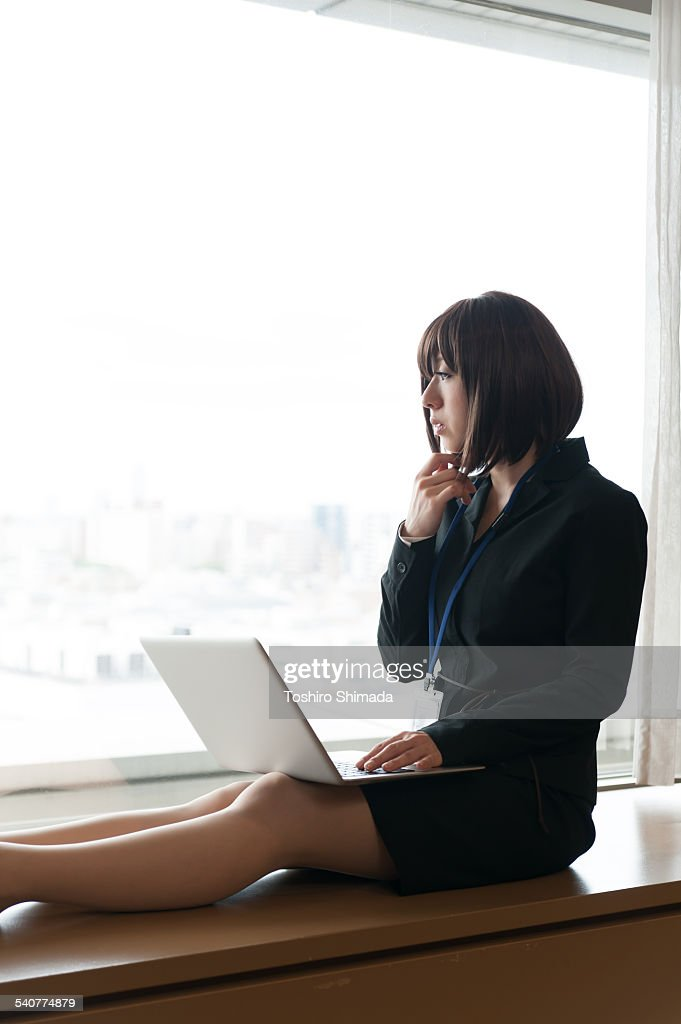 A woman laptopping at window : Stock Photo