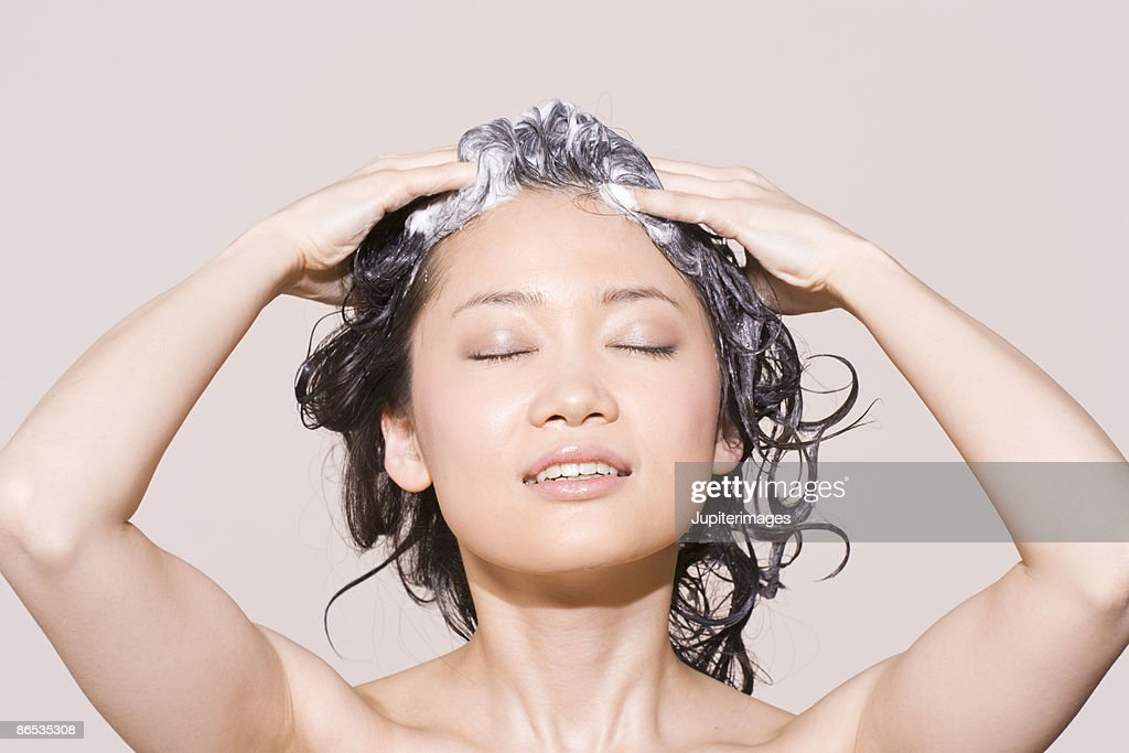 Woman lathering shampoo : Stock Photo