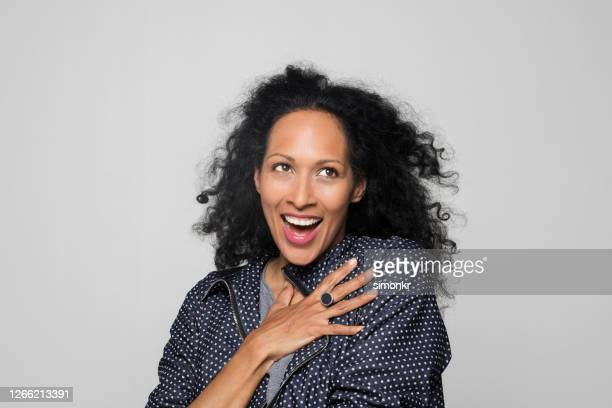 woman laughing against grey background - one mature woman only stock pictures, royalty-free photos & images