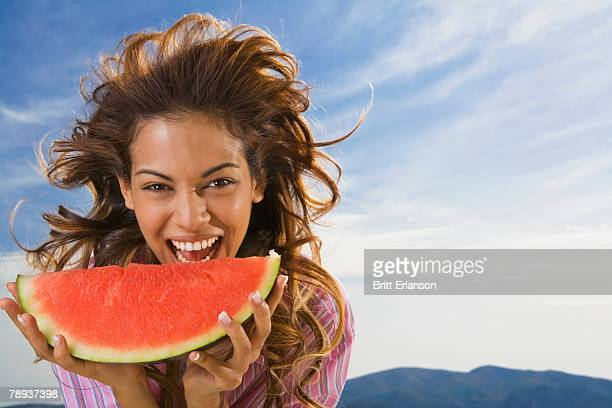 Woman laughing and eating watermelon outdoors.