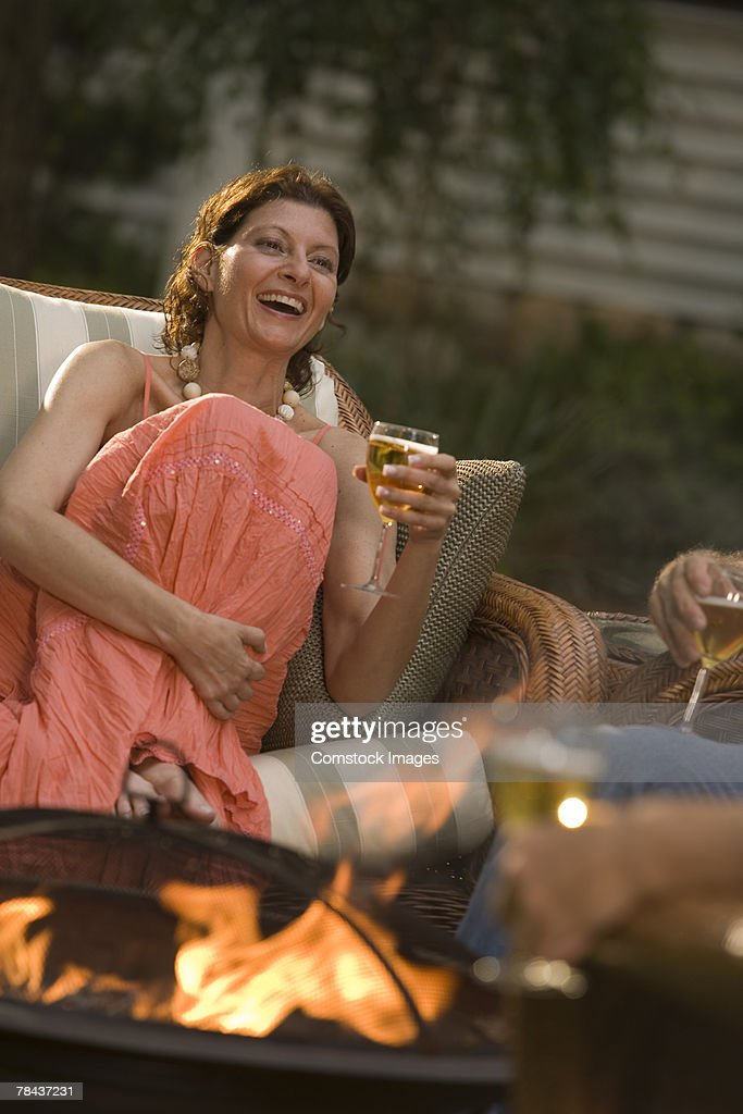 Woman laughing and holding a glass of wine : Stockfoto