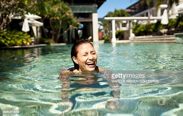 woman laughing and swimming at luxury resort - candid stock pictures, royalty-free photos & images