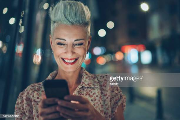 Woman laughing at a message outdoors at night