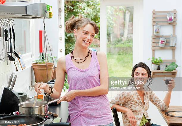 woman laughing at friends while preparing food. - newpremiumuk stock pictures, royalty-free photos & images