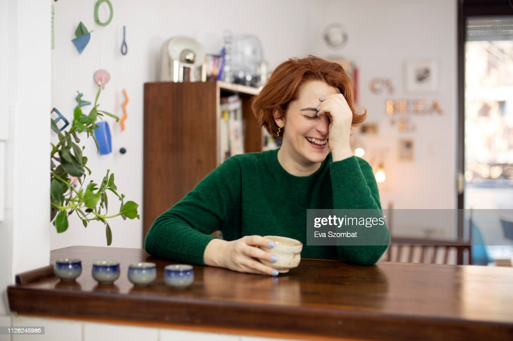 woman laughing at home drinking tea : Stock-Foto