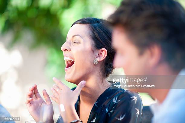 Woman laughing at table outdoors
