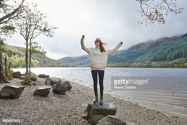 woman laughing by the side of a loch - human arm stock-fotos und bilder