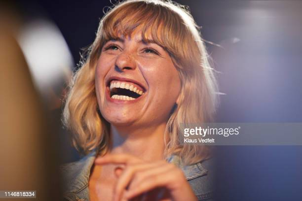 woman laughing during comedy movie - ridere foto e immagini stock