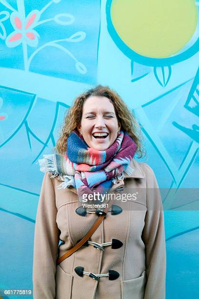 Woman laughing, graffiti in the background