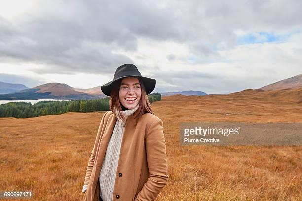woman laughing in autumnal landscape - coltrui stockfoto's en -beelden