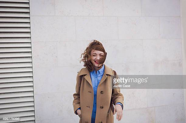 woman laughing in the wind in font of a wall