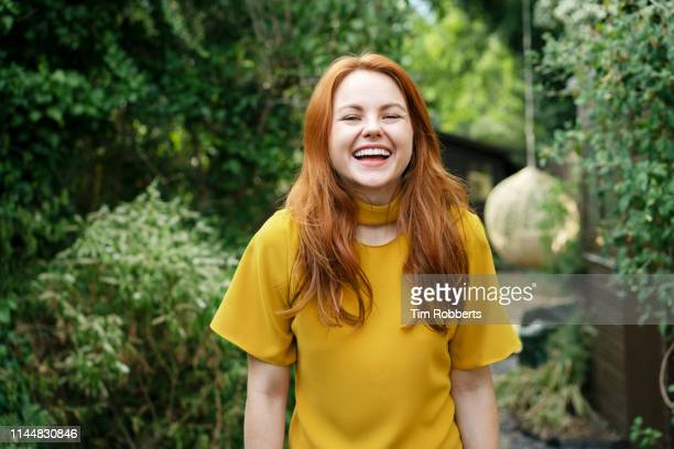 woman laughing, looking at camera - stralende lach stockfoto's en -beelden