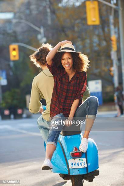 Woman laughing on back of scooter