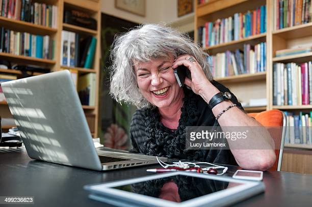 woman laughing on the phone at home office - netherlands stock pictures, royalty-free photos & images