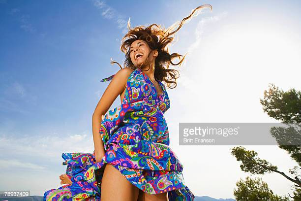 Woman laughing outdoors in a colorful dress.