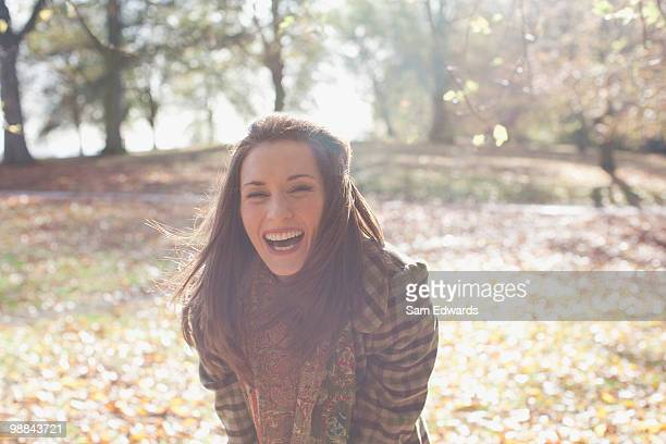 Woman laughing outdoors in autumn leaves