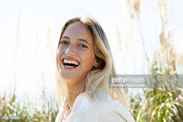 Woman laughing outdoors, portrait