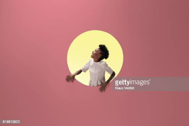 woman laughing, placed inside round opening in coloured wall - yellow dress stock pictures, royalty-free photos & images