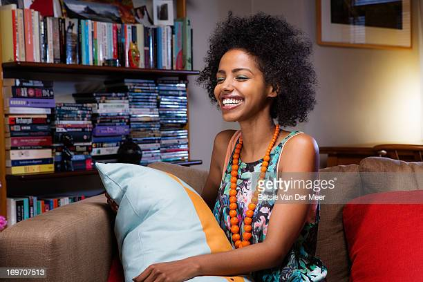 woman laughing sitting on sofa watching film. - sleeveless top stock pictures, royalty-free photos & images