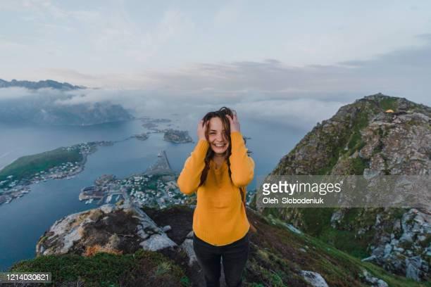 mulher rindo em pé na montanha reinebringen na ilha lofoten - cultura norueguesa - fotografias e filmes do acervo