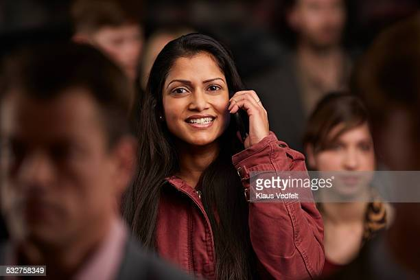 Woman laughing while on he phone, in crowd