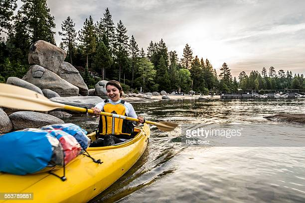 Woman laughing while paddling a kayak.