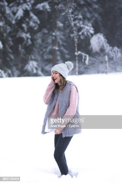 Woman Laughing While Standing On Snow Covered Field