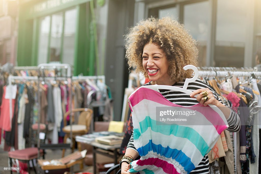 Woman laughing while trying on clothes at market : Stock Photo