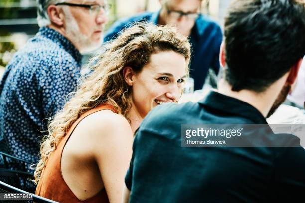 Woman laughing with boyfriend during celebration dinner with friends