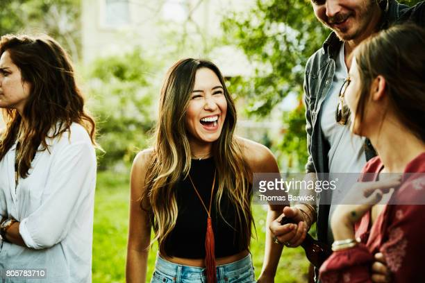 Woman laughing with friends during backyard party on summer evening