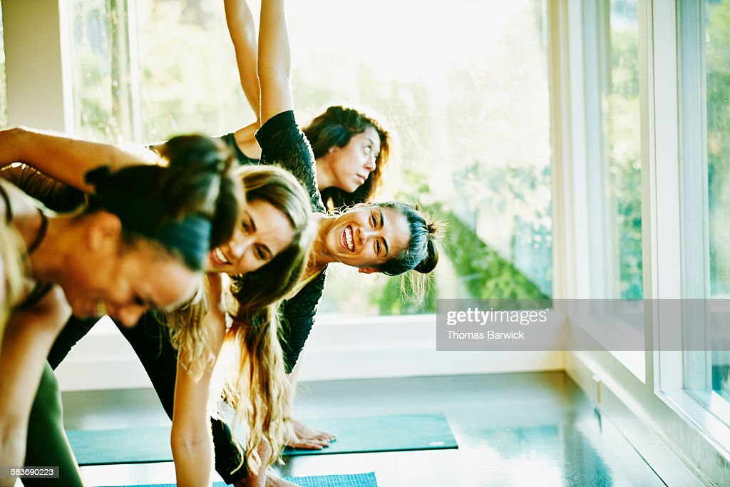 Woman laughing with friends during yoga class : Stock Photo