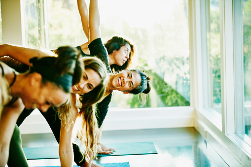 Woman laughing with friends during yoga class - gettyimageskorea
