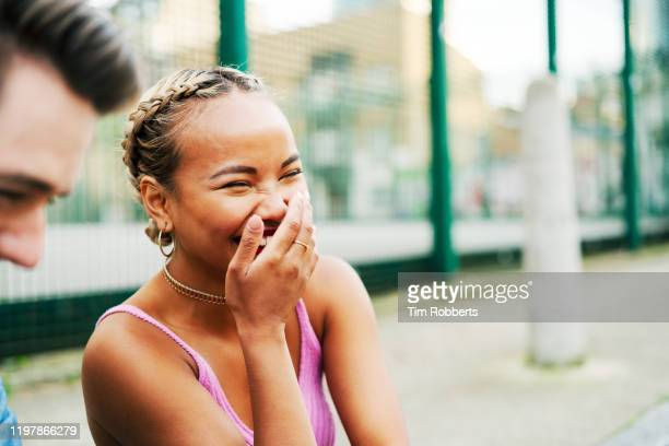 woman laughing with hand over mouth - young women stock pictures, royalty-free photos & images