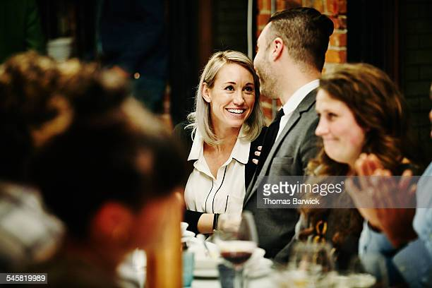 Woman laughing with man during dinner party