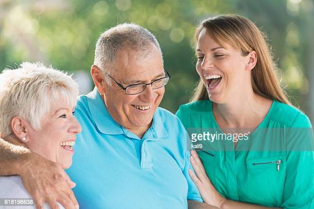 Woman laughing with senior parents outdoors