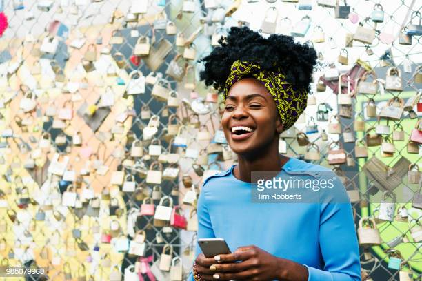 Woman laughing with smart phone infront of padlock fence