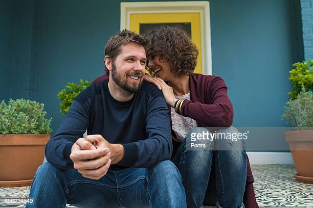 woman laughing with spouse while sitting on porch - 35 39 years stock pictures, royalty-free photos & images