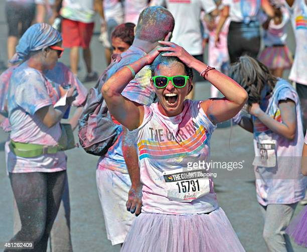 A woman laughs after having blue chalk thrown on her at one of four chalk stations along the five kilometer course at The Color Run presented by...
