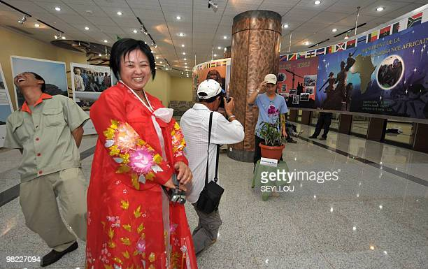 A woman laughs as North Korean workers take pictures in the hall of the 'African Renaissance Monument' on April 2 2010 in Dakar on the eve of the...