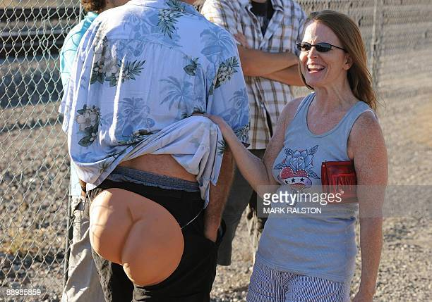 A woman laughs as residents of Laguna Niguel prepatre to expose their buttocks during the 30th annual Mooning of the trains event along a stretch of...