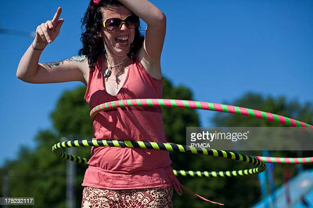 Woman laughs as she attempts to learn to hula hoop in a park in Brighton 2010