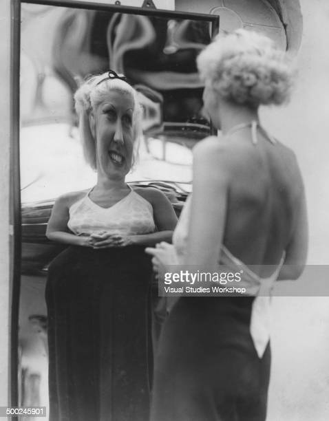 Woman laughs at her reflection in a distorting mirror at a resort fun house early to mid 20th century