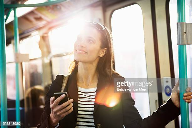 Woman laughs at message on mobile phone, standing on train