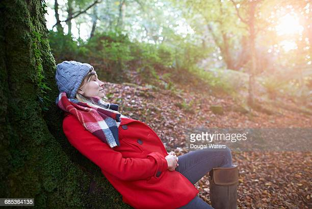 Woman laying against tree trunk in forest.
